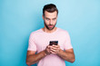 Leinwanddruck Bild Photo of attractive guy holding telephone hands open mouth reading bad news negative post comments followers wear casual pink t-shirt isolated blue color background