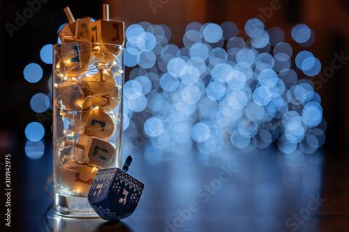 Fototapeta jewish holiday Chanukah/Hanukkah with wooden dreidels / sovivon (spinning top) in the glass over glitter shiny background. Traditional invitation card design obraz