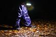 canvas print picture - Kind läuft mit Taschenlampe durch dunkle Nacht im Wald mit blauer Regenhose und Gummistiefeln auf feuchtem Waldboden mit buntem Laub allein und voller Angst als Nachtwanderung