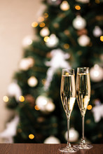 New Year Champagne. Christmas Composition With Champagne In Interior And White Christmas Tree Decorations. Bokeh Garland Lights And Holiday Atmosphere.