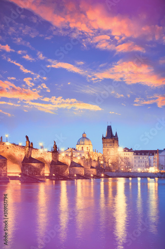 Charles Bridge reflected in Vltava river in Prague on a sunset. Vertical image with neon color toning with golden, purple, violet and blue colors.