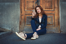 Young Woman In Denim Clothing Sitting On Ground Over Old Fashioned Historical Wooden Door And Grey Concrete Wall Background And Feeling Confused With Phone. Travels In Details And Emotions Concept