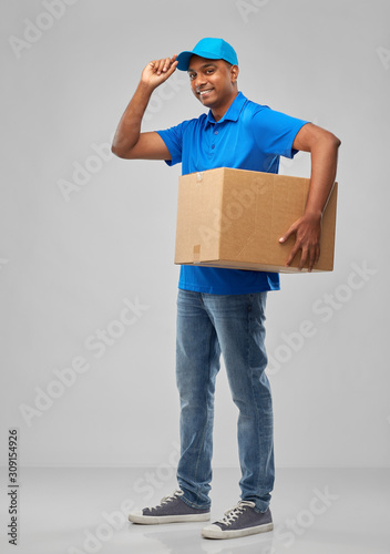 Cuadros en Lienzo mail service and shipment concept - happy indian delivery man with parcel box in