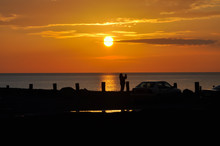 Photographer In Silhouette Taking A Photo Of A Glorious Sun Setting Over The Irish Sea In Aberystwyth Ceredigion Wales UK