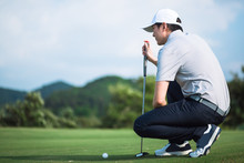 Side View Professional Golfer Check Line For Putting Golf Ball On Green Grass. Golf Player Crouching And Study The Green Before Putting Shot.