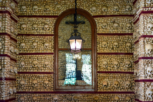 Fotografia  Faro, Algarve / Portugal - Skulls and bones are embedded in the wall, a lantern