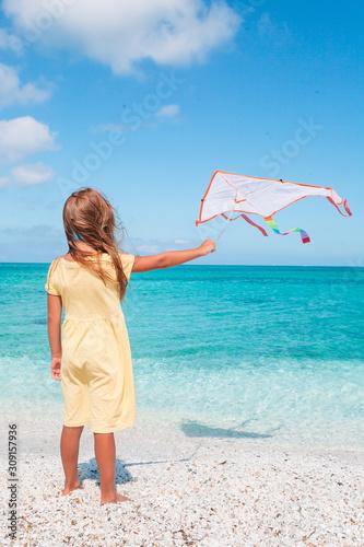 Little running girl with flying kite on tropical beach Wallpaper Mural