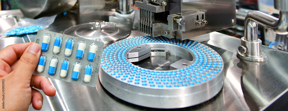 Fototapeta Hand holding blue capsule pack at medicine pill production line, Industrial pharmaceutical concept.banner side