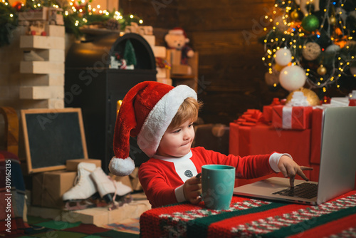 obraz dibond On-line Christmas shopping for kids. Little kid is wearing Santa clothes sitting by his laptop. Santa helper using notebook.