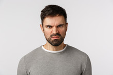 Close-up Studio Shot Hateful And Outraged, Aggressive Scary Bearded Adult Man In Grey Sweater, Grimacing, Wrinkle Nose And Look With Disgrace, Disdain Or Scorn, Standing Bothered White Background