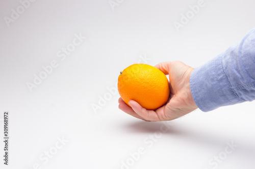 Photo Naranja cogida por la mano de una persona adulta