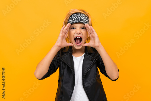 cool blond boy in a leather jacket and a white T-shirt with a bandana shouts on Canvas Print