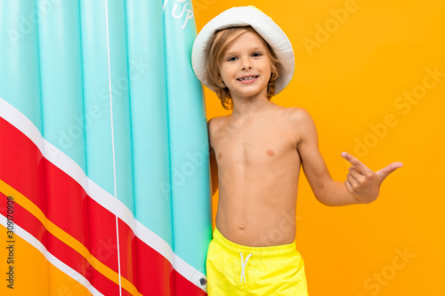 Obraz attractive European blond boy in a summer panama with an inflatable swimming board on a yellow background - fototapety do salonu