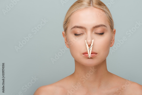 Fototapeta attractive and naked young woman with wooden pin on nose and closed eyes isolated on grey obraz na płótnie