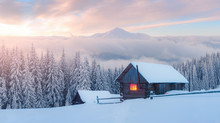 Fantastic Winter Landscape With Wooden House In Snowy Mountains. Hight Mountain Peaks In Foggy Sunset Sky. Christmas And Winter Vacations Holiday Concept