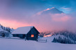 canvas print picture - Fantastic winter landscape with wooden house in snowy mountains. Hight mountain peaks in foggy sunset sky. Christmas and winter vacations holiday concept