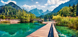 Wooden bridge over the Jasna lake. Panoramic summer view of Julian Alps, Gozd Martuljek location, Slovenia, Europe. Bright landscape of Triglav National Park. Traveling concept background.