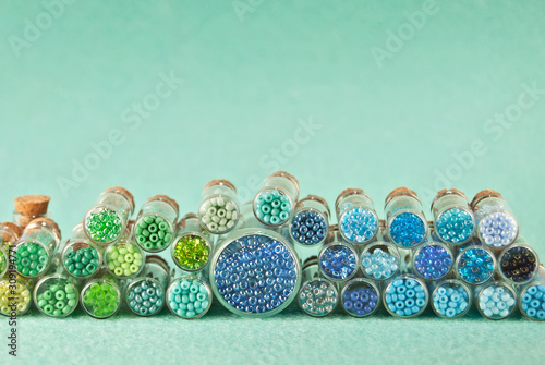 Blue, green, yellow and purple beads in glass jars on a bright cyan background Canvas Print