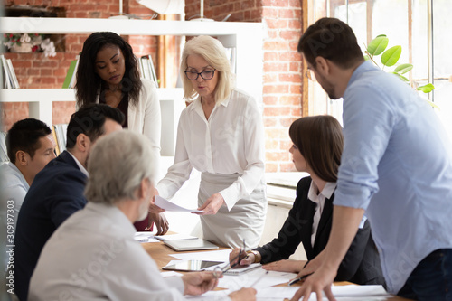 Fotomural Diverse team and aged boss do paperwork analyzing financial report