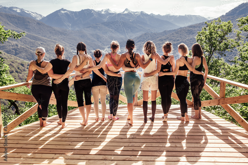 Fototapeta Rear view of a group of slim body-positive sportive active friendly women doing fitness and yoga together among mountain ecologically clean nature. Ecological Sports Tourism Concept