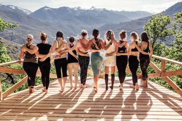 Rear view of a group of slim body-positive sportive active friendly women doing fitness and yoga together among mountain ecologically clean nature. Ecological Sports Tourism Concept