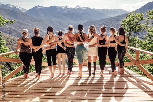 Fototapeta Rear view of a group of slim body-positive sportive active friendly women doing fitness and yoga together among mountain ecologically clean nature. Ecological Sports Tourism Concept obraz