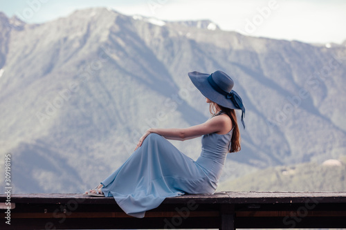 Obraz na plátně  Rear view of a slim beautiful young woman in a hat sitting on a bench overlooking a gorgeous mountain landscape and admiring it on a sunny warm summer day while relaxing
