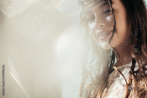 smiling ethnic girl with braids in hairstyle posing in white boho dress on grey with lens flares