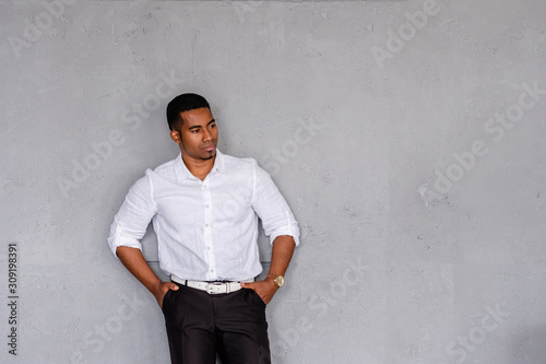 Successful handsome confident African American businessman posing against the background of a gray wall in formal clothes Fototapete