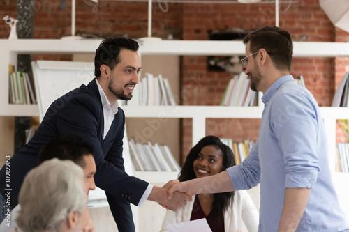 Fototapeta Middle east appearance and caucasian businessmen shake hands during meeting obraz na płótnie