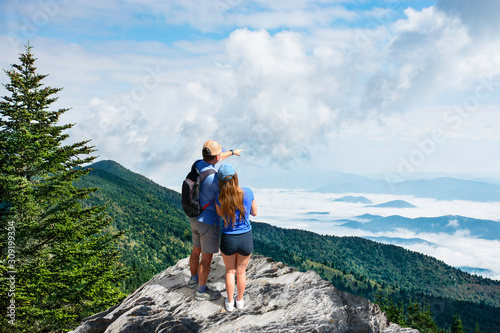 Couple on top of mountain looking at beautiful landscape Canvas Print