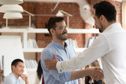 Middle east appearance boss praising employee express respect shaking hands