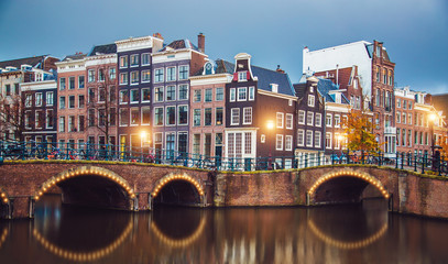 Fototapeta Architektura Amsterdam canal, bridge and typical houses, boats and bicycles during evening twilight blue hour, Holland, Netherlands