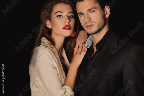 attractive woman hugging handsome man in suit isolated on black - 309204102