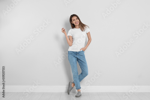 Obraz Young woman in stylish jeans near light wall - fototapety do salonu