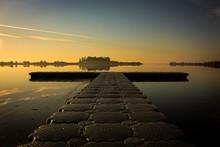 Boardwalk Over The Calm Sea Under The Sunset Sky