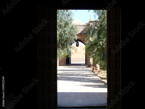 Obraz na plátně  Tree lined tiled Walkway to arched door with view of Sand Dunes - Nomad Palace,