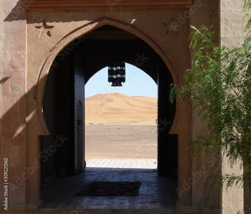 Obraz na plátně  Arched door with tiled entryway,  view of sunlit Sahara sand dunes, hanging lant