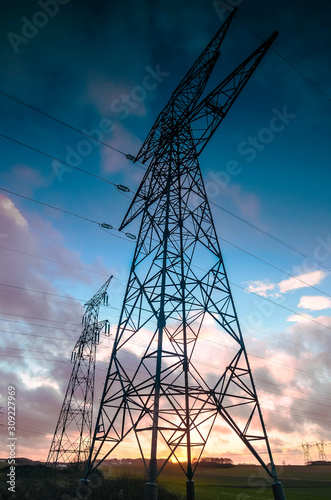 Fotografía set of electric pylons at sunset