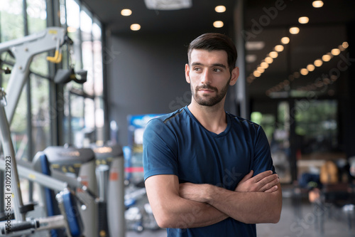 Obraz na płótnie Caucasian man with beard in blue color sportswear standing and putting hands on waist in gym or fitness club