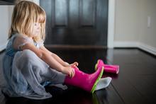 Preschool Girl Practices Putting On Rain Boot