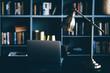 Dark interior with blue decor and modern furniture. Modern creative workspace background. Front view computer with dark blue bookcase.