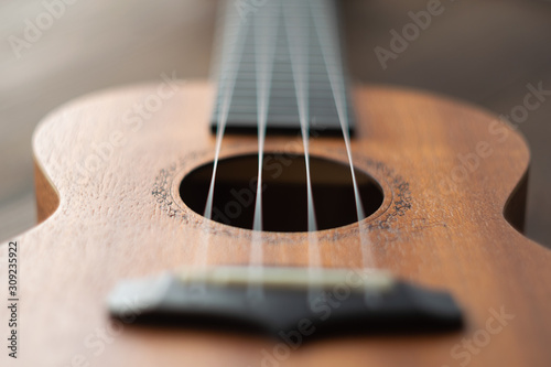 Photo  Defocused ukulele strings body, soundhole, bridge and neck on brown wooden background