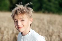 Portrait Of Smiling Boy Standing In Oat Field