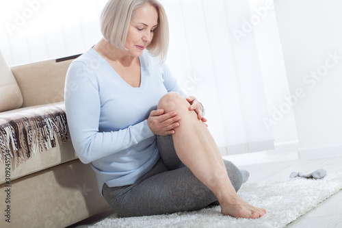 Fotomural Middle-aged woman suffering from pain in leg at home, closeup