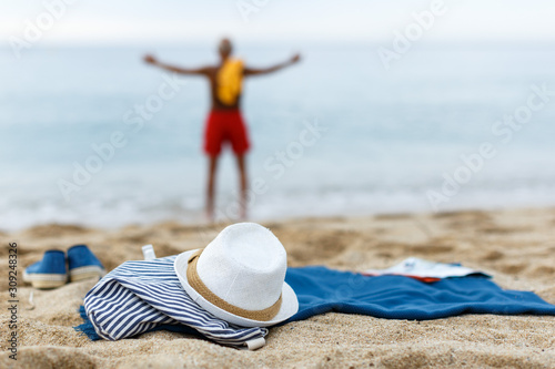 Glad male resting. Clothes on the sand near sea