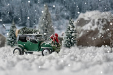 Miniature Classic Car Carrying A Christmas Tree On Snowy Winter Landscape