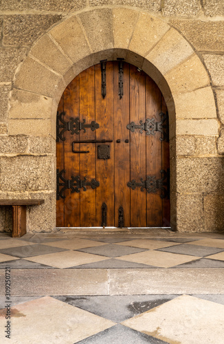 Solid wood and reinforced arched door inside historic monastery in Guimaraes Canvas Print