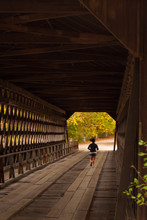 A Lone Female Jogger Runs Through A Covered Bridge.