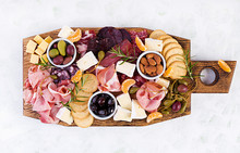 Antipasto Platter With Ham, Prosciutto, Salami, Cheese,  Crackers And Olives On A Light Background.  Christmas Table. Top View, Overhead